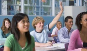Close-up af unge i et klasselokale - en rækker en hånd i vejret