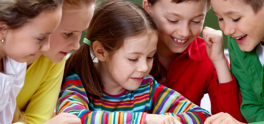 Gruppe af børn der læser i bog